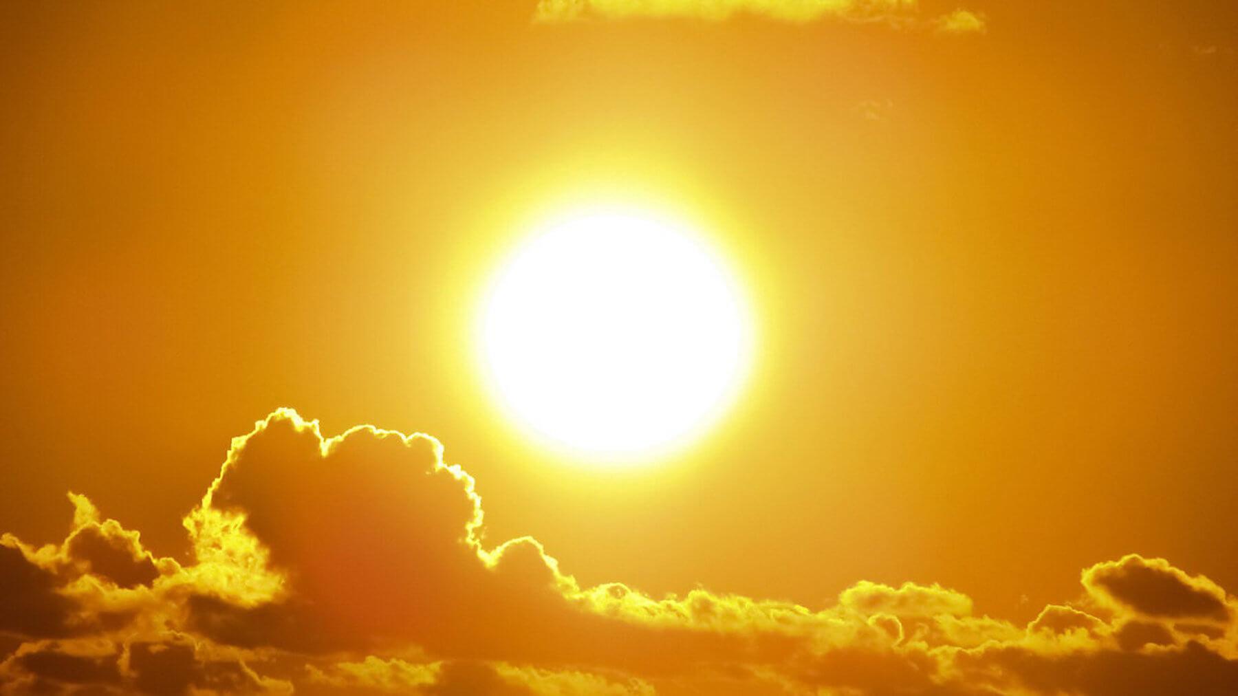 Bright orange sun reflecting on clouds below